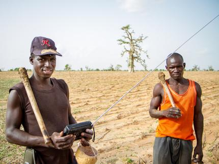 Farmers in the Sahelian village of Diouna in southern Mali listen to the radio as they prepare their field for planting. Photo: F. Fiondella (IRI)